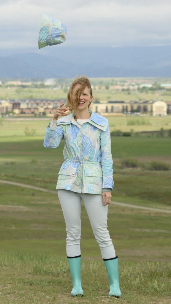 woman wearing refashioned caftan into a jacket, throwing hat