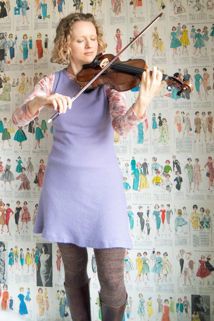 A flexible wardrobe requires mixing pieces that work for your hobbies. Woman playing violin while wearing orchid sweater dress styled with printed rayon t-shirt