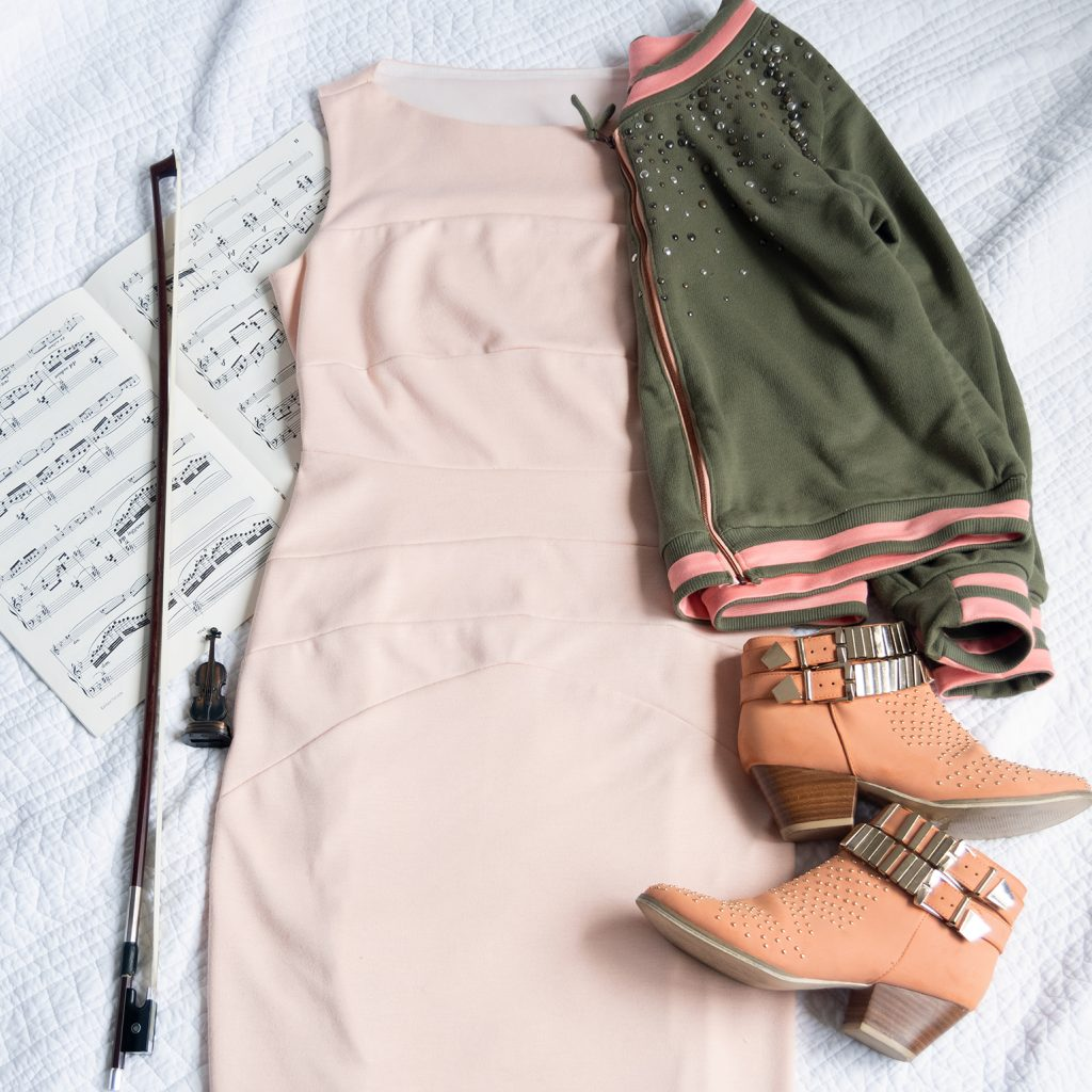 flatlay of peach booties, violin bow, music, blush ponte dress, and french terry bomber jacket