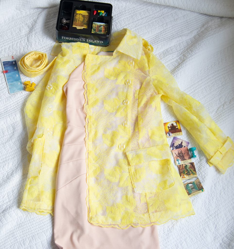 flatlay of yellow embroidered organza trench coat and Forbidden Island board game