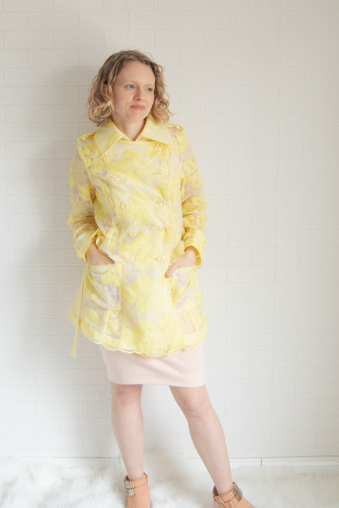 pockets on yellow embroidered organza trench coat, blush pink dress, and peach booties