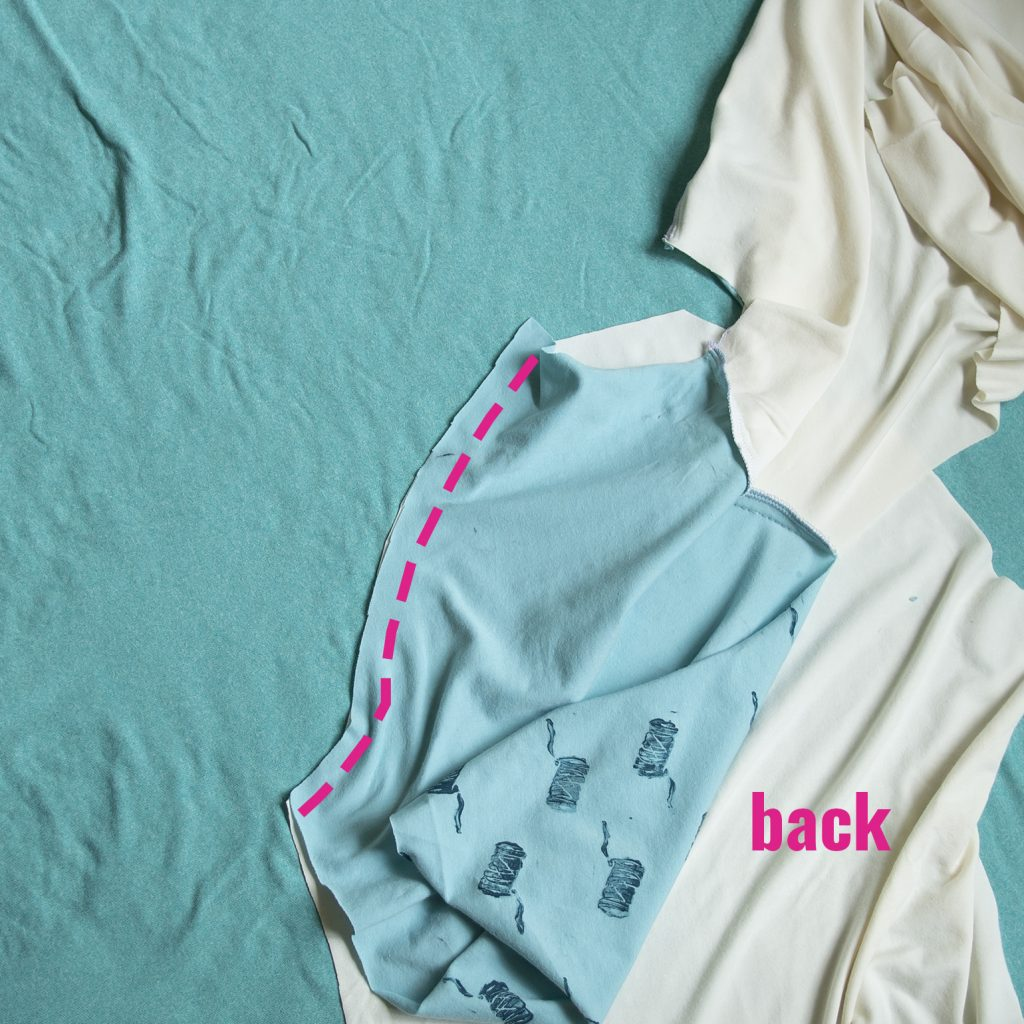 aback and sleeve pieces of a diy raglan tee: pink line showing where to sew a back sleeve seam on a diy raglan tee