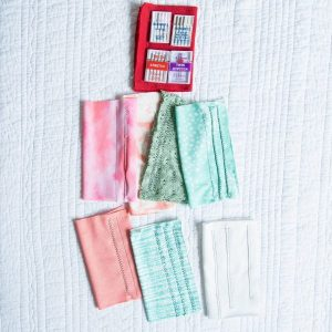 flatlay of different knit fabric samples with stitching and needles for stretch fabrics