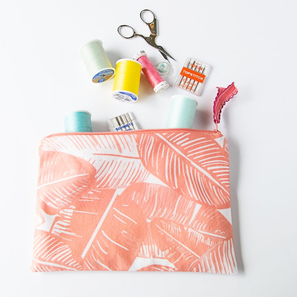 zipper bag holding thread, scissors, and needles for sewing