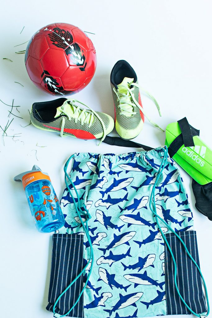 drawstring backpack with water bottle, cleats, shin guards, and soccer ball
