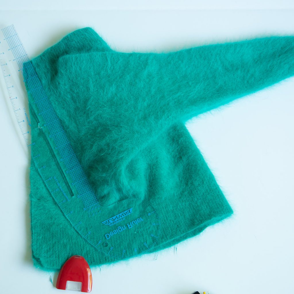 drawing a chalk line for cutting on a refashioned sweater