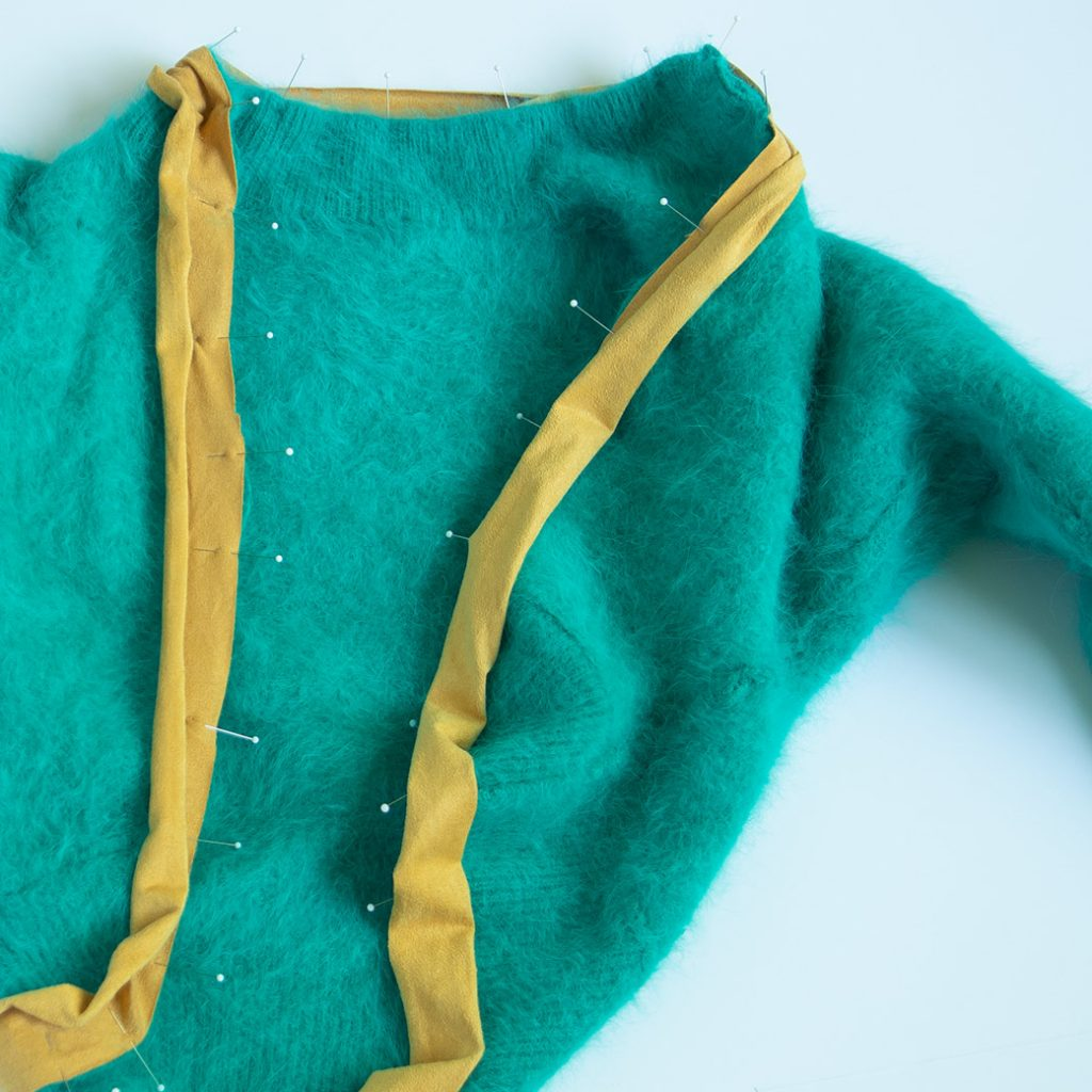 pinning sueded knit binding to sweater in refashioned sweater shrug tutorial