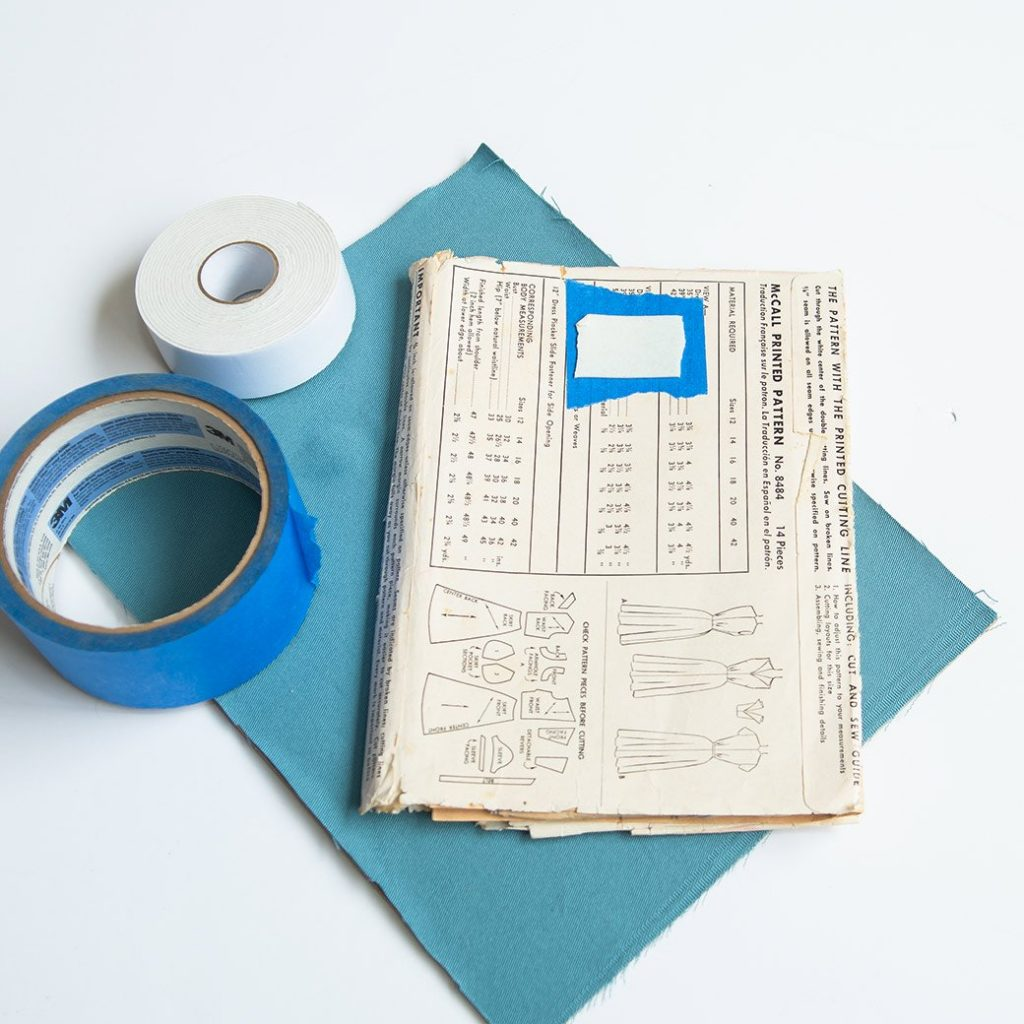 adding tape to back of vintage pattern for sewing room decor