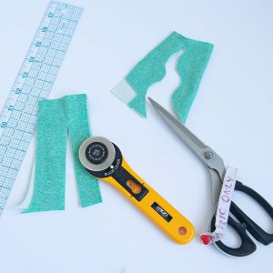 ruler, rotary cutter and sewing shears with fabric samples